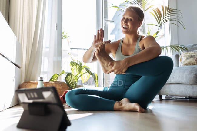 Улыбающаяся женщина, занимающаяся йогой, изучая цифровой планшет дома — стоковое фото