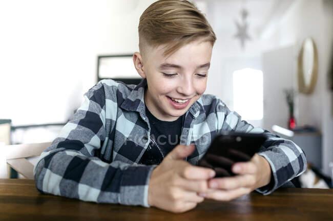 Sonriente niño usando el teléfono inteligente mientras está sentado en la mesa en la sala de estar - foto de stock