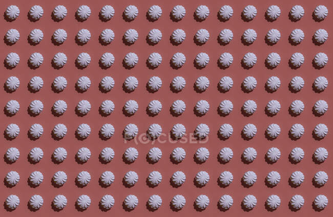 Pattern of rows of pink zefirs against brown background — Stock Photo