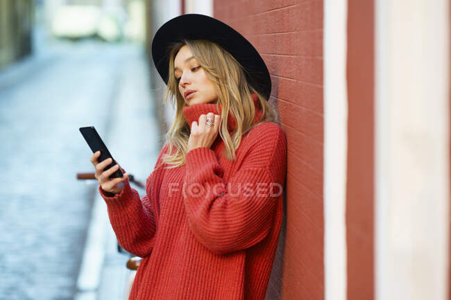Young woman using smart phone while leaning on wall — Stock Photo