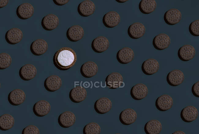 Pattern of rows of brown cookies with single one having white top — Stock Photo