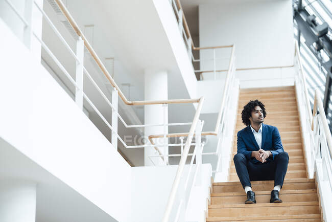 Thoughtful male professional looking away while sitting on staircase in office — Stock Photo