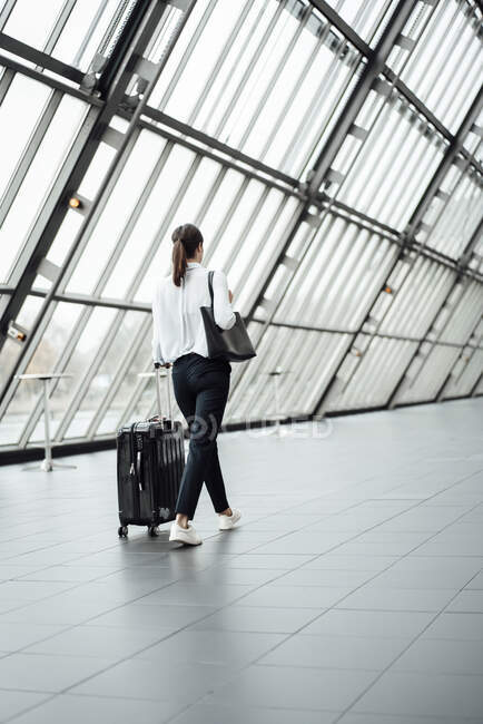 Female entrepreneur with suitcase walking in corridor of office — Stock Photo
