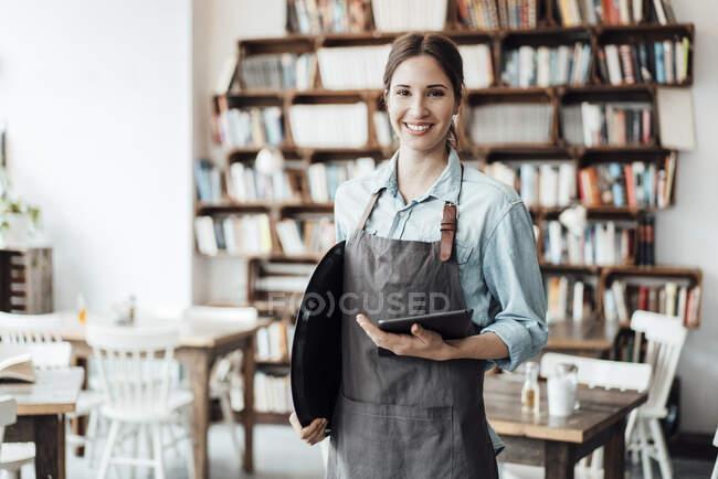 Посмішка жіночого підприємця з цифровим планшетом і підносом у кав'ярні. — стокове фото