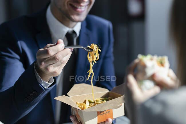 Empresario comiendo fideos mientras está sentado con su colega en la cafetería en la oficina - foto de stock