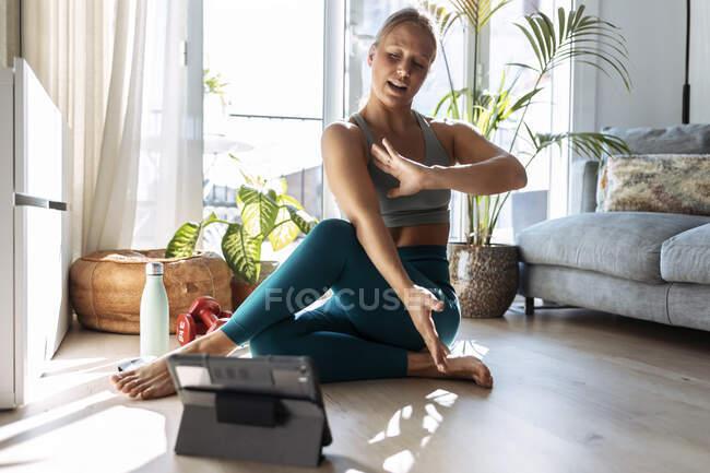 Юна жінка займається йогою, навчаючись на цифровій планшеті, що сидить удома. — стокове фото