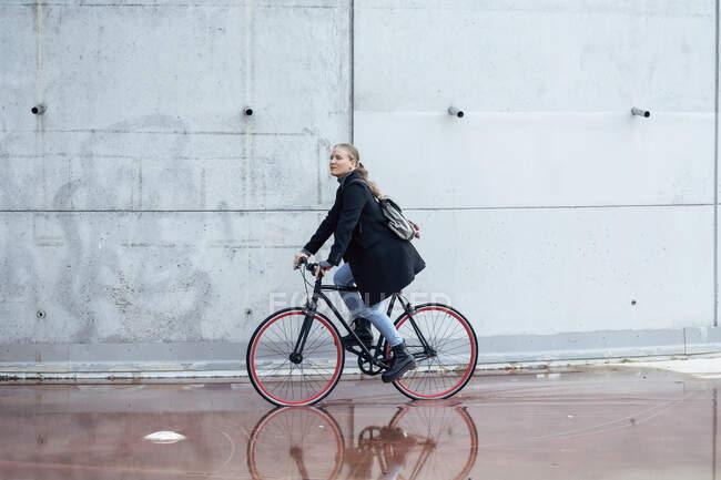 Mulher fazendo ciclismo na estrada molhada por parede — Fotografia de Stock