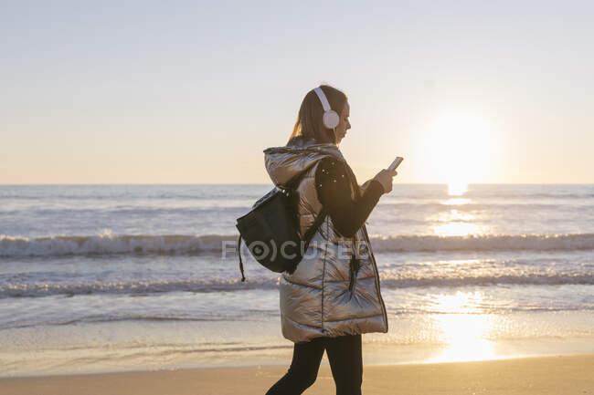Mujer escuchando música y usando un teléfono inteligente mientras camina en la playa al atardecer - foto de stock