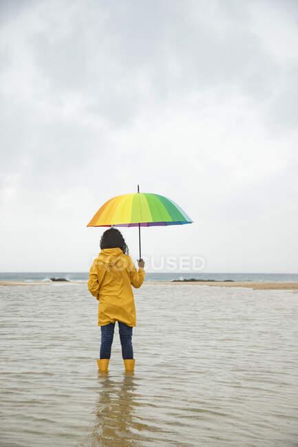 Jovem mulher segurando guarda-chuva enquanto em pé na água na praia — Fotografia de Stock