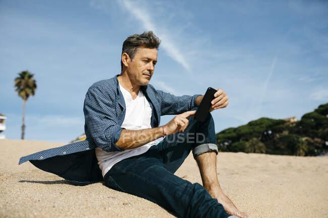 Homem maduro usando telefone celular enquanto sentado na praia durante o dia ensolarado — Fotografia de Stock