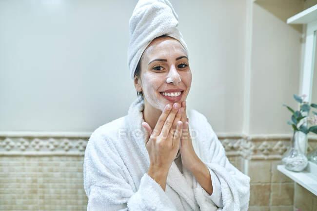 Улыбающаяся женщина наносит крем на лицо в ванной комнате — стоковое фото