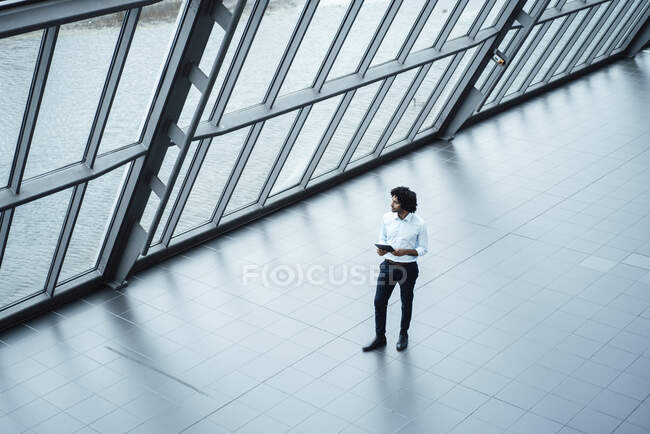 Young male professional with digital tablet walking by roof in office corridor — Stock Photo