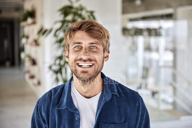 Hombre feliz con ojos grises en el loft - foto de stock
