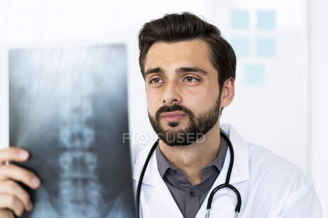 Красивый медицинский работник, анализирующий рентген в больнице — стоковое фото