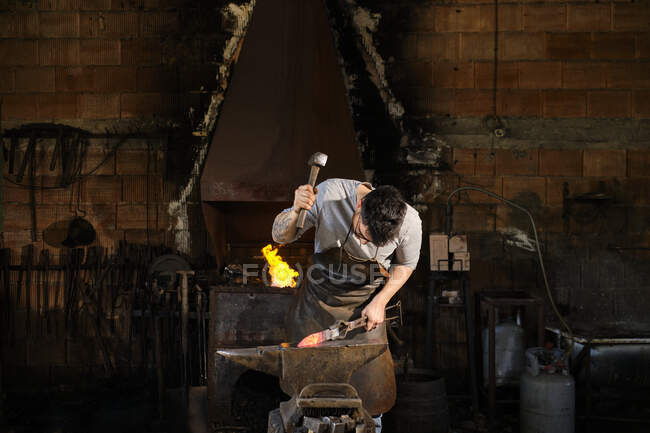 Metallarbeiter schmiedet Metall mit Hammer in Schmiede — Stockfoto