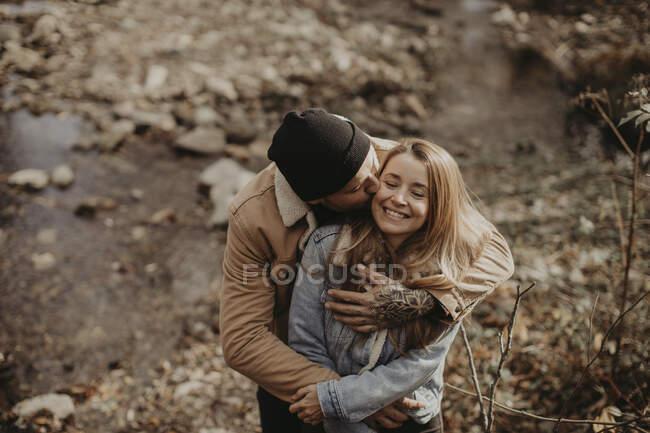 Гіпстер з в'язаною капелюхом цілує дівчину в лісі. — стокове фото