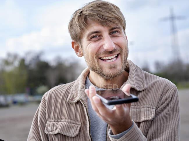 Uomo sorridente che invia messaggi vocali attraverso il telefono cellulare — Foto stock