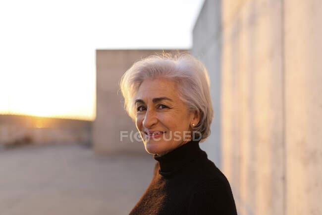 Доросла жінка з сивим волоссям, що посміхається перед стіною. — стокове фото
