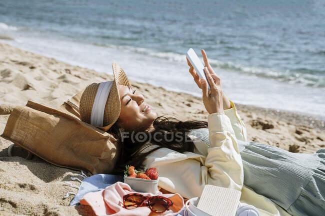 Mujer usando un teléfono inteligente mientras está acostada en la playa - foto de stock