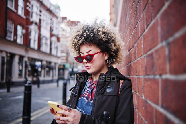 Giovane donna che indossa occhiali da sole utilizzando smartphone mentre si appoggia alla parete durante le vacanze a Chinatown — Foto stock