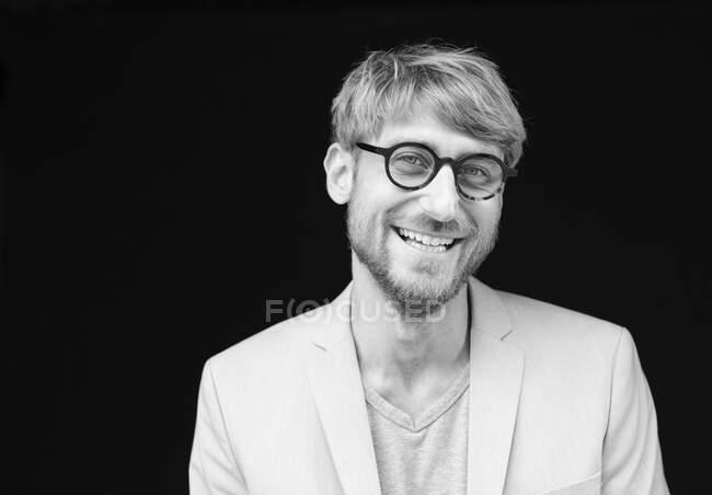 Счастливчик в очках на чёрном фоне — стоковое фото