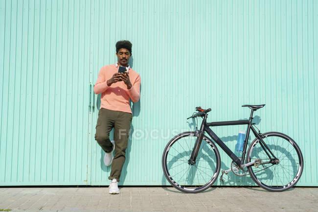 Hombre guapo de pie en bicicleta mientras usa el teléfono inteligente durante el día soleado - foto de stock