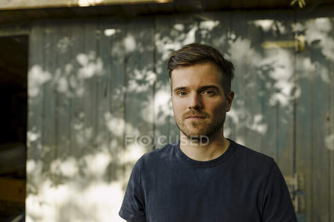 Man with hair stubble standing in front of house — Stock Photo
