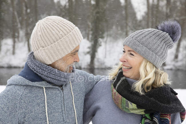 Happy senior couple in warm clothing looking at each other during winter — Stock Photo