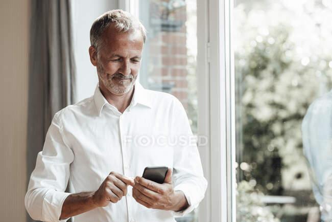 Homem maduro usando telefone inteligente em pé pela janela em casa — Fotografia de Stock