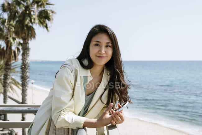 Linda turista feminina apoiando-se no corrimão pela praia — Fotografia de Stock