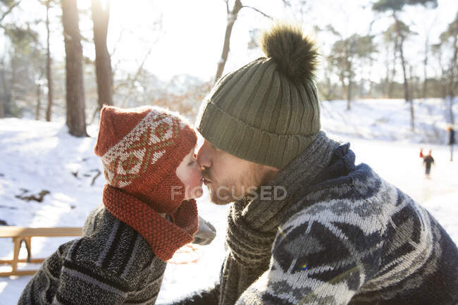 Boy kissing father during winter — Stock Photo