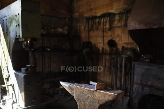 Молот на ковадло в магазине коваля — стокове фото