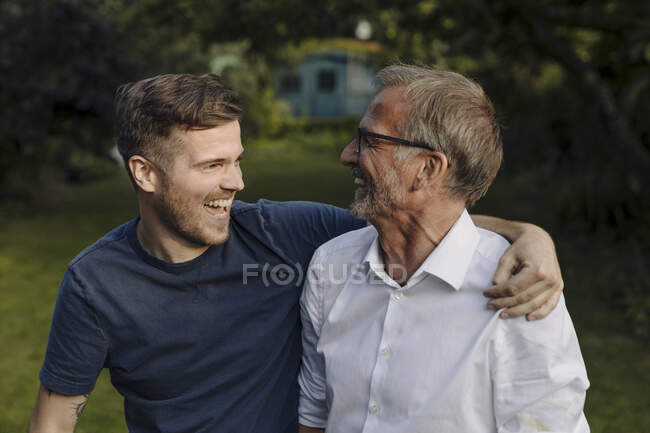 Веселий чоловік з обіймами біля батька. — стокове фото