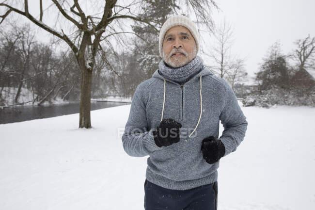 Senior man wearing warm clothing running at park — Stock Photo