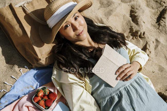 Metà donna adulta sdraiata sulla sabbia in spiaggia durante la giornata di sole — Foto stock