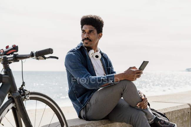 Hombre guapo con bigote mirando hacia otro lado mientras sostiene el teléfono inteligente en la pared de contención - foto de stock