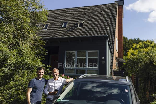 Sorridente padre e figlio in piedi a casa vicino alla macchina durante la giornata di sole — Foto stock