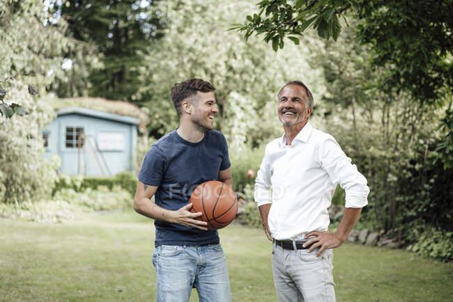 Padre sorridente con le mani sull'anca in piedi con figlio che tiene la pallacanestro in cortile — Foto stock