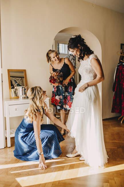 Счастливые подруги готовят невесту в домашней комнате — стоковое фото