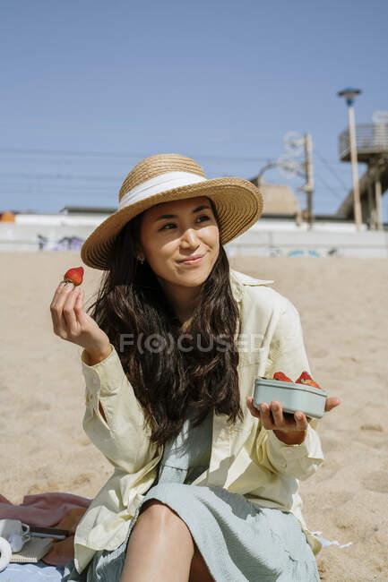 Donna che tiene le fragole mentre si siede in spiaggia nella giornata di sole — Foto stock