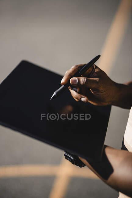 Hombre con pluma digitalizada usando tableta durante el día soleado - foto de stock