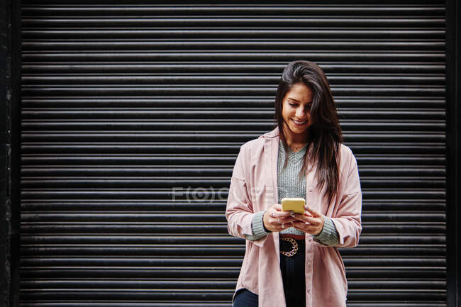 Smiling woman using mobile phone while standing in front of shutter — Stock Photo