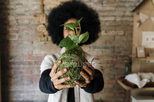 Чоловік, що тримає рослину кокедама перед лицем удома. — стокове фото