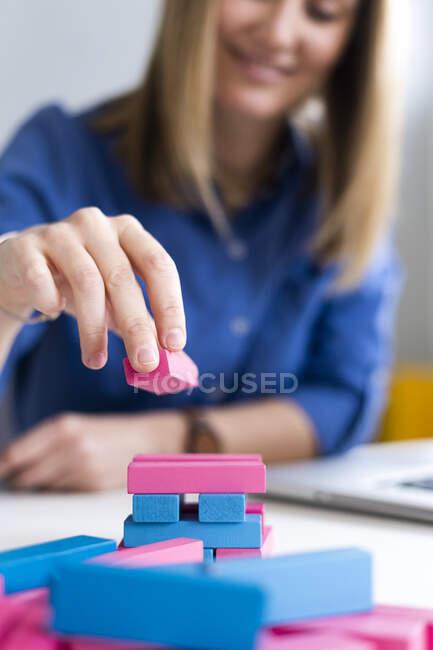 Empresária organizando blocos de construção na mesa no escritório — Fotografia de Stock
