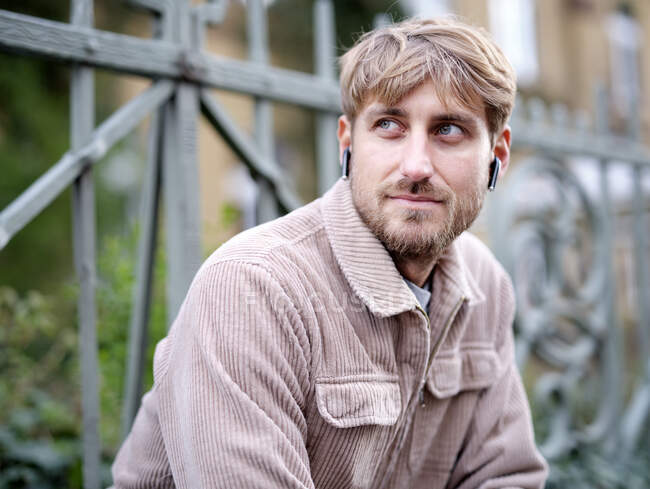 Bearded man with in-ear headphones looking away in front of railing — Stock Photo