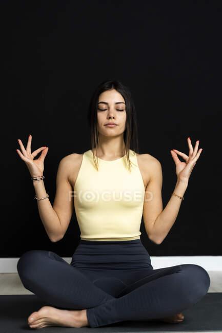 Женщина, сидящая в студии йоги — стоковое фото