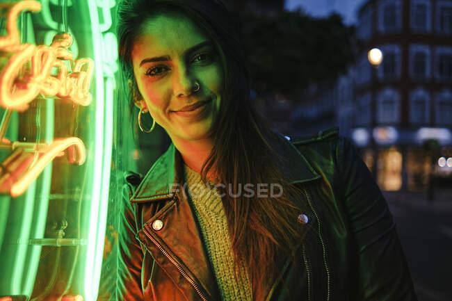 Beautiful woman with jacket standing by illuminated light — Stock Photo