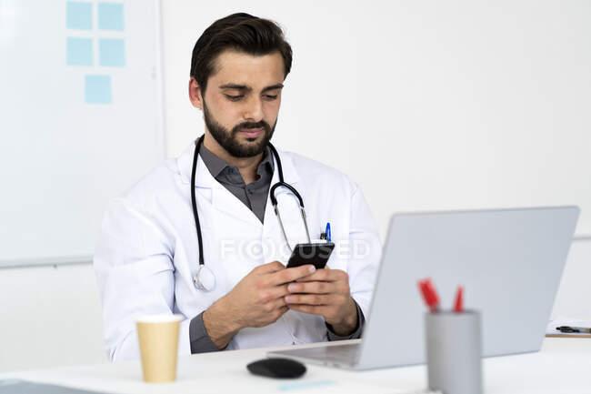 Médico masculino usando teléfono móvil mientras está sentado en el escritorio - foto de stock