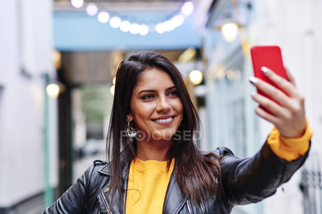Beautiful woman smiling while taking selfie on mobile phone in city — Stock Photo