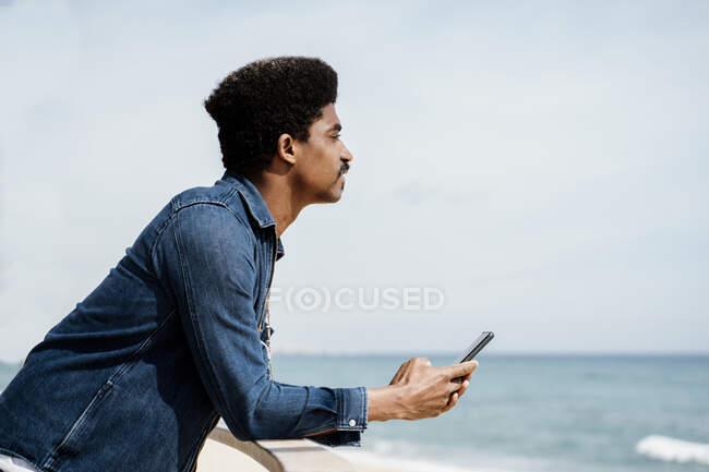 Homem de camisa jeans olhando para longe enquanto segurando o telefone celular pelo céu — Fotografia de Stock